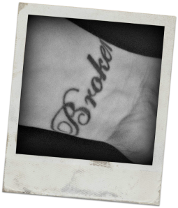PHOTOGRAPH: A tattoo on a woman's wrist that reads 'Broken'.